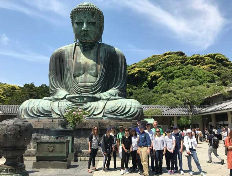 Photo of students by a Buddha statue
